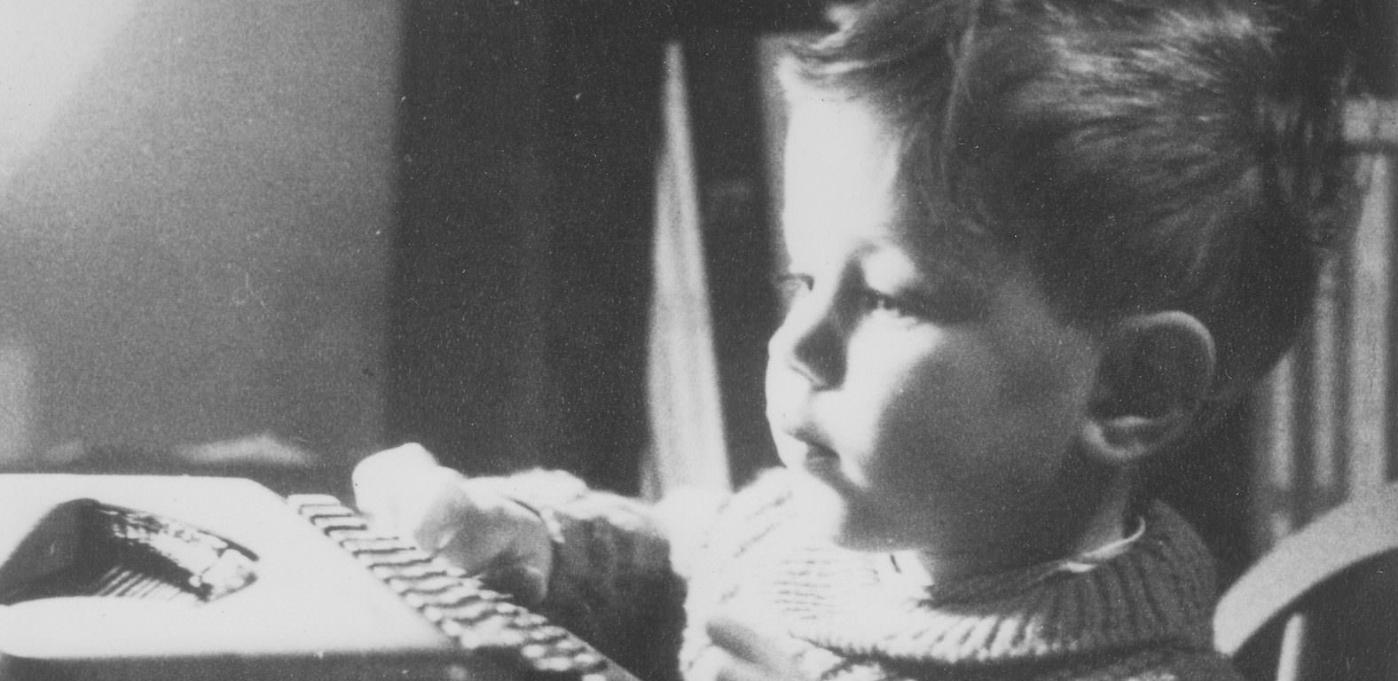 A young boy typing on an old typewriter